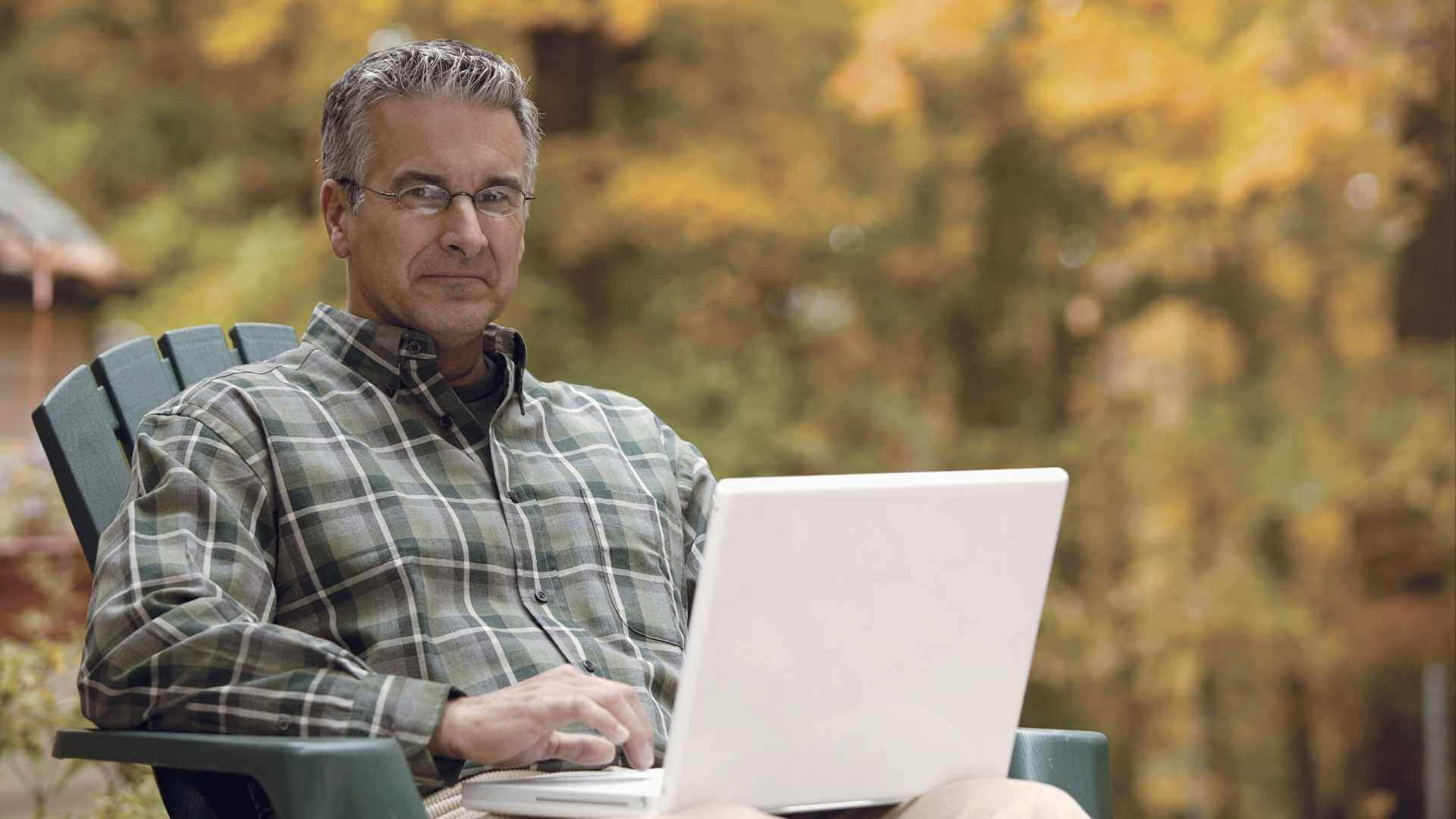 men using his laptop by the yard