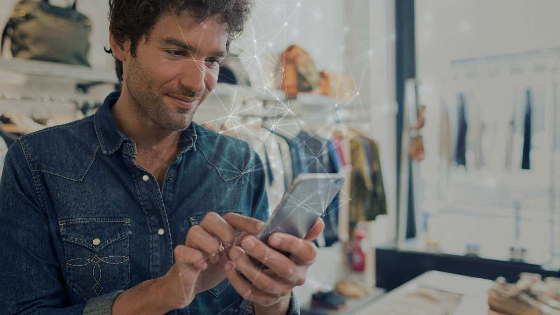 men looking at his phone inside a fashion store